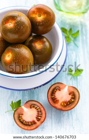 Overhead view of a bowl of ripe tomatoes, a variety of tomato developed and grown in Spain with a sweet intense flavor and dark coloring - stock photo