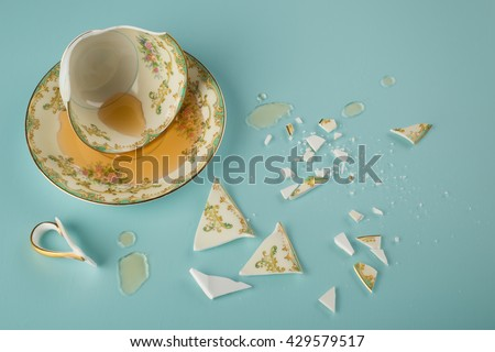 Overhead view of a Broken Elegant Vintage China Teacup with saucer dish, spilled tea and fractured shards of sharp glass fragments scattered on teal colored kitchen table background.  Horizontal  - stock photo