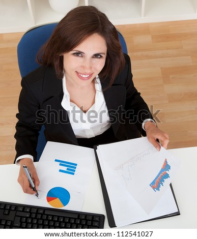 overhead view of a businesswoman working in office - stock photo