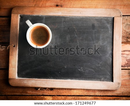 Overhead view of a cup of coffee on an old school slate with a wooden frame and blank copyspace on the cleaned chalkboard lying on a rustic wooden table - stock photo