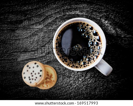 Overhead view of a cup of freshly brewed hot espresso coffee served on a weathered grunge rustic wooden table wiith two iced biscuits - stock photo