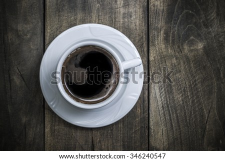 Overhead view of a freshly brewed mug of  black  coffee on rustic wooden background - stock photo
