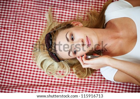 Overhead view of a gorgeous blonde woman lying on her back on a fresh red and white checked cloth with her hair spread around her talking on a mobile - stock photo