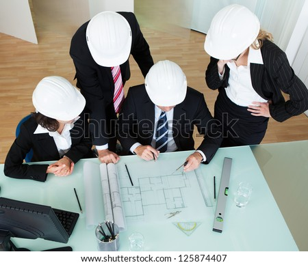 Overhead view of a group of architects or structural engineers discussing a blueprint laid out on the table in front of them - stock photo