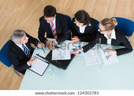 Overhead view of a group of diverse business executives holding a meeting around a table discussing graphs showing statistical analysis - stock photo