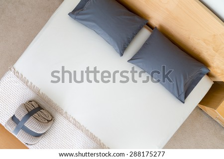 Overhead view of a neat king size bed in a hotel or house with black pillows on a white counterpane with a folded and strapped rug at the food and a wooden headboard - stock photo