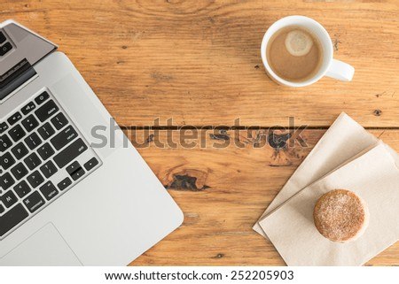 Overhead view of a notebook computer, fresh muffin and a white cup of coffee on a rustic wooden cafe table. - stock photo