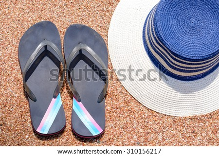 Overhead view of a pair of casual slip slops and sunhat on a tropical beach conceptual of a summer holiday or vacation - stock photo