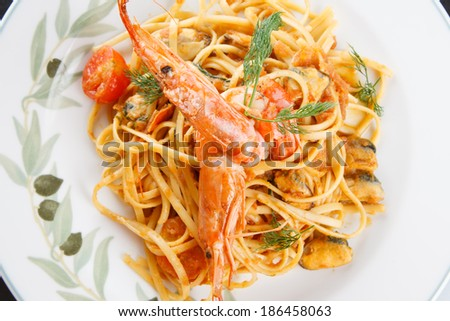 Overhead view of a plate of savory Italian seafood linguini pasta with shrimp and mussels sauteed with ouzo, spring onion and shrimp bisque - stock photo