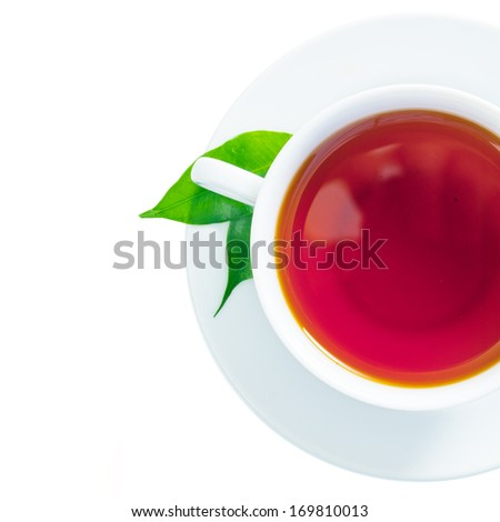 Overhead view of a refreshing cup of freshly brewed black tea with two green tea leaves in the saucer isolated on white - stock photo