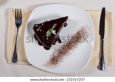Overhead view of a slice of rich tasty freshly baked chocolate cake with icing dripping down the sides served on a plate at table - stock photo