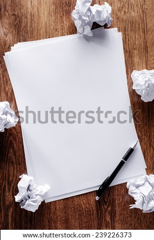Overhead view of a stack of blank white sheets of paper surrounded with crumpled remnants screwed up in frustration on a wooden desk - stock photo