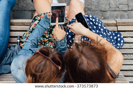 Overhead view of a teenage girl using mobile phone and tablet - stock photo