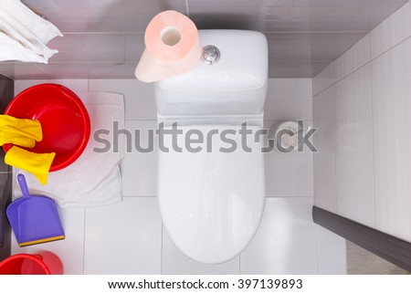 Overhead view of a toilet with a colorful array of assorted household cleaning products and a roll of soft pink toilet paper - stock photo