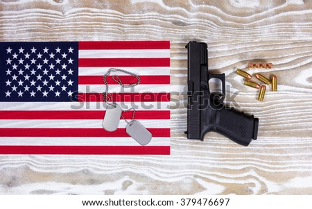 Overhead view of a United of America flag,   ID tags, pistol and bullets on faded white wood.  - stock photo
