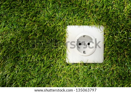 Overhead view of a white plastic outdoor electrical power socket embedded in green grass with copyspace alongside - stock photo
