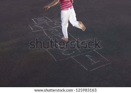 Overhead view of a young girl skipping through a game of hopscotch marked out on an asphalt surface - stock photo