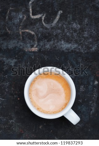 Overhead view of an aromatic frothy cup of freshly brewed cappuccino standing on a grungy old blackboard slate with chalk scribblings and copyspace - stock photo