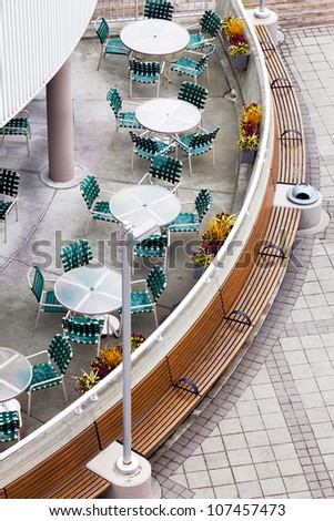 Overhead view of an outdoor city cafe or restaurant.  Top view, looking down onto tables, chairs and architecture.  - stock photo
