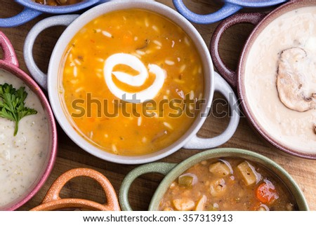 Overhead view of assorted soup in bowls with handles with focus to a cup of chicken broth with wild rice garnished with a twirl of sour cream - stock photo