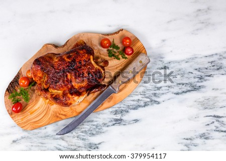 Overhead view of barbecued chicken with vegetables, herbs and large cutting knife on wooden server with white marble underneath.  - stock photo