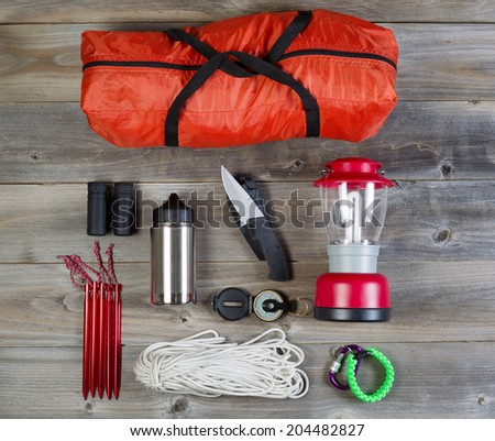 Overhead view of basic hiking gear placed on weathered wooden boards. Items include tent inside of bag, pegs, compass, canteen, rope, knife, case, lantern and binoculars.  - stock photo
