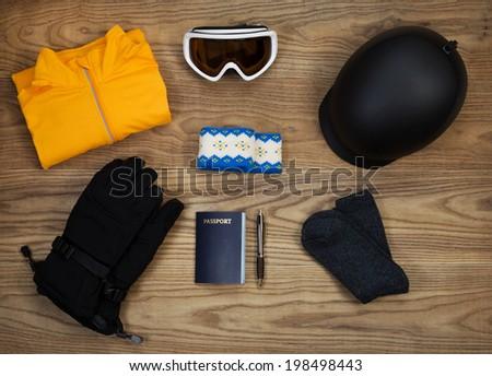 Overhead view of basic ski and snow board accessories placed on rustic wooden boards. Items include helmet, goggles, gloves, sweat shirt, head band, wool socks, and passport.   - stock photo