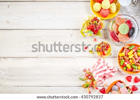 Overhead view of bowls filled with candy and other yummy confections beside glass jar with rolled licorice - stock photo