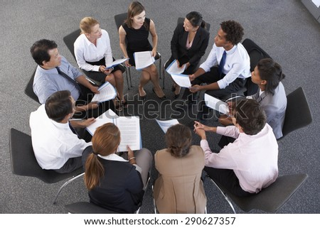 Overhead View Of Businesspeople Seated In Circle At Company Seminar - stock photo