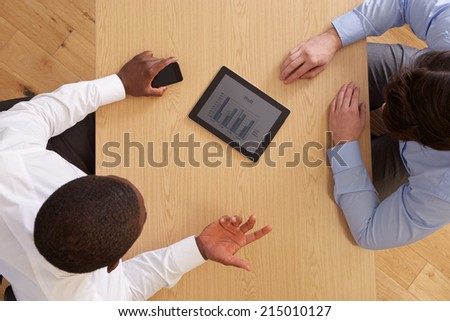 Overhead View Of Businesspeople With Digital Tablet At Desk - stock photo