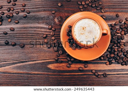 overhead view of Ceramic orange cup of coffee with foam and coffee beans, standing on wooden table - stock photo