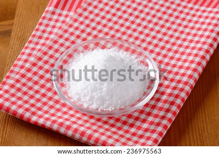 overhead view of coarse salt in the glass bowl with fabric linen - stock photo