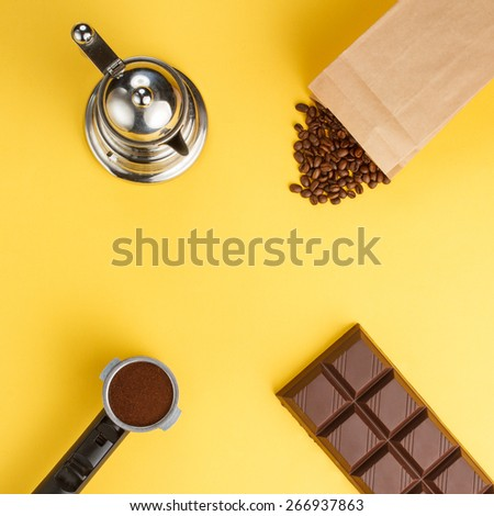 Overhead view of coffee machine filter holder, coffee beans, bar of chocolate, coffee-pot on yellow background - stock photo