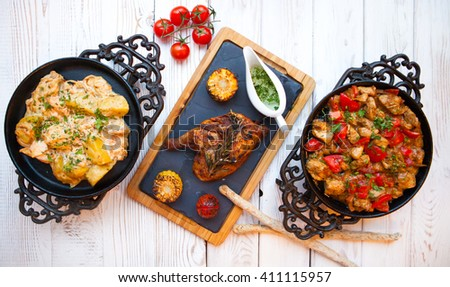 Overhead view of colorful roast vegetables, savory sauces and salt served with grilled chicken leg on a white wooden background   - stock photo