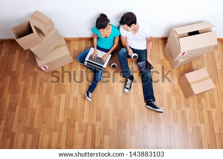 overhead view of couple sitting on floor together using computer wireless internet while moving into new home - stock photo
