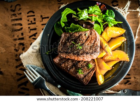 Overhead view of delicious,grilled beef steak with roasted pumpkin and fresh green herb salad on an old wooden packing case with printed text - stock photo