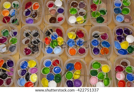 Overhead view of dozens of well used cups of vividly colored acrylic or tempera paint and paintbrushes  arranged in rows of containers. - stock photo