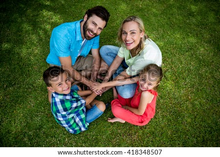 Overhead view of family huddling hands while sitting on grass at yard - stock photo
