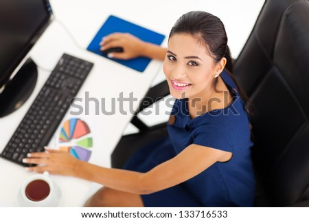 overhead view of female corporate worker working by her desk - stock photo