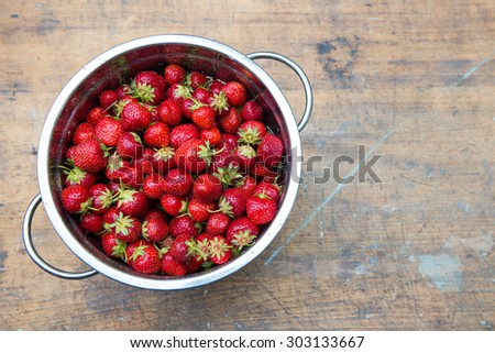 Overhead view of freshly picked strawberries in colander, on rustic wooden background - stock photo