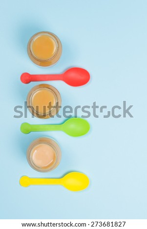 Overhead view of glass jars of baby food with colorful spoons on blue background - stock photo