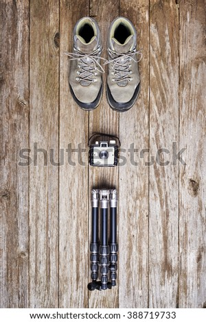 overhead view of hiking boots, vintage camera, and tripod. - stock photo