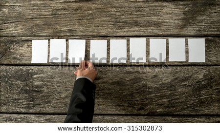 Overhead view of male hand in elegant business suit placing nine blank white cards in a row on a rustic textured wooden boards. With copy space ready for your text or promotion. - stock photo