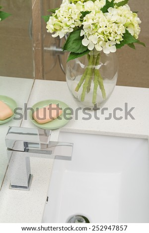 Overhead view of modern bathroom tap and basin with accessories - stock photo