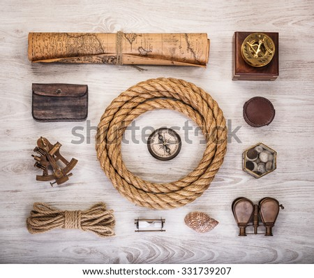 Overhead view of pirate or sailor gear laid out for a backpacking trip on a old wood floor. Items include, rope, compass, money, map, binoculars, sextant , shell. Stories background.  - stock photo