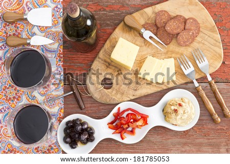 Overhead view of savory snacks on a rustic table with two glasses and a bottle of red wine and havarti cheese,spicy dried sausage,olives, red bell pepper and hummus with cheese cutters for serving - stock photo