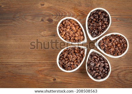 Overhead view of several varieties of fresh roasted coffee beans on a brown wooden background with copy space. - stock photo