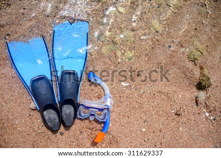 Overhead view of skin diving gear lying on a beach with a snorkel, goggles and fins or flippers conceptual of a tropical summer vacation at the seaside - stock photo