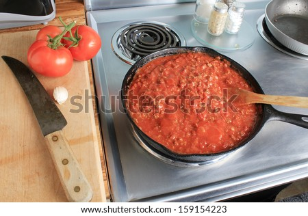 Overhead view of spaghetti sauce in cast iron skillet on stainless steel electric stove.  Fresh tomatoes on cutting board with clove of garlic and kitchen knife. - stock photo