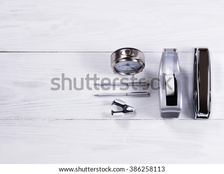 Overhead view of stainless steel stationery items consisting of stapler, tape dispenser, pens, stapler remover and clock on white wood.  - stock photo